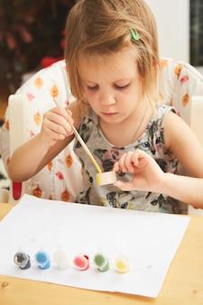 Malowanie dziecka. szczęśliwa dziewczyna w wieku przedszkolnym trzymając pędzel