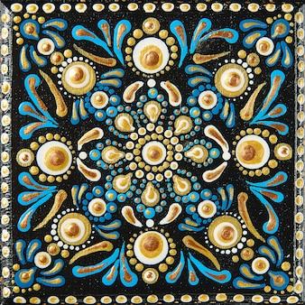 Malowanie kropek mandali na płytkach drewnianych. piękna mandala ręcznie malowana kolorowymi kropkami na czarnym drewnie.