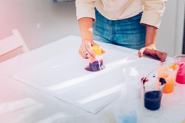 Malowanie marmuru. twórczy obiecujący artysta w dżinsach wykonujący marmurowy obraz na białym papierze