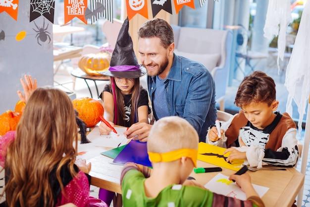 Malowanie nietoperzy. uśmiechnięty przystojny brodaty ojciec pomaga swoim dzieciom malować nietoperze i pająki na halloween