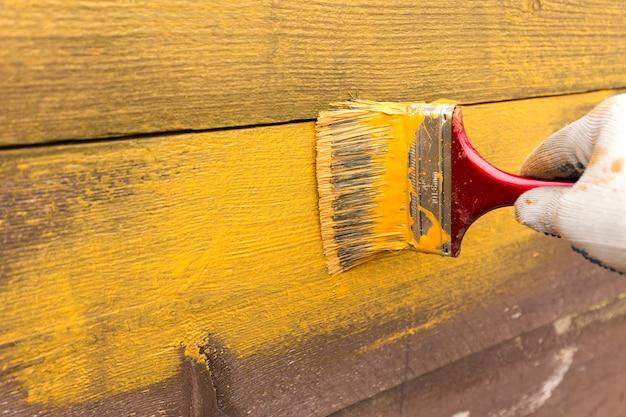 Malowanie ogrodzenia żółtą farbą w ogrodzie za domem.