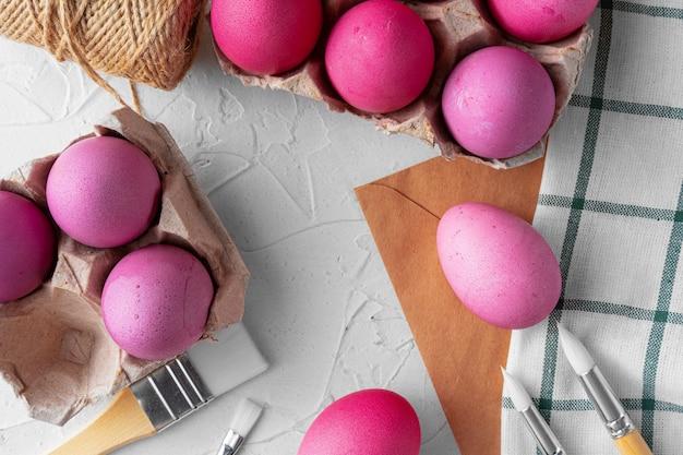 Malowanie pisanek na różowo na białym stole, widok z góry