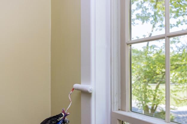 Malowanie przez pracownika renowacji domu za pomocą wałka malarskiego kolor biały wykończenie ramy okiennej