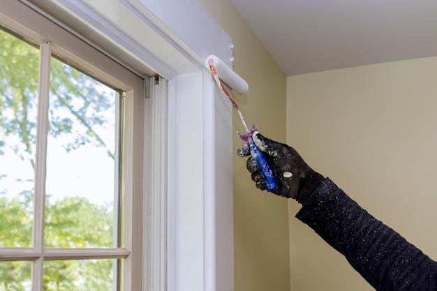 Malowanie przez pracownika za pomocą wałka malarskiego na warstwie w kolorze białym wykończenie ramy okiennej przy renowacji domu