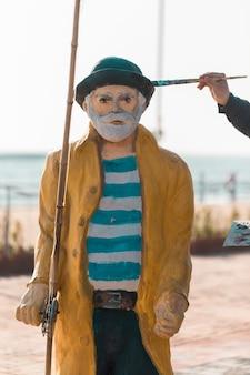 Malowanie rzeźby starego rybaka.