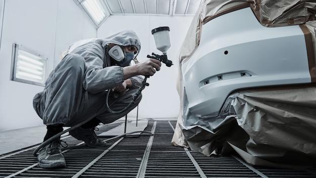 Malowanie samochodów i naprawa samochodów. mechanik samochodowy w białym kombinezonie maluje samochód z rozpylaczem aerografu w komorze lakierniczej