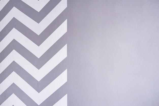Malowanie ściany Taśmą Maskującą. Białe Paski Zygzakowate Na Szarej ścianie. Gotowa ściana. Premium Zdjęcia