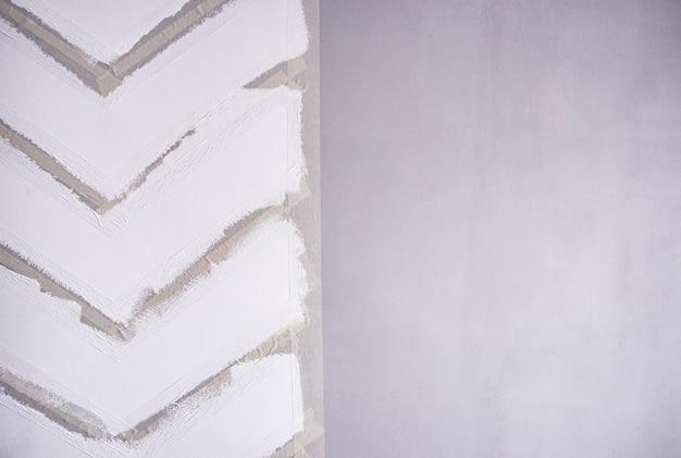 Malowanie ściany taśmą maskującą. białe paski zygzakowate na szarej ścianie.
