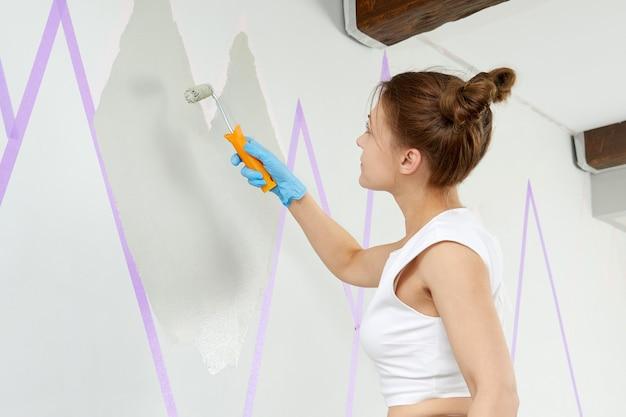 Malowanie ściany wałkiem i taśmą maskującą stojąc na drabinie