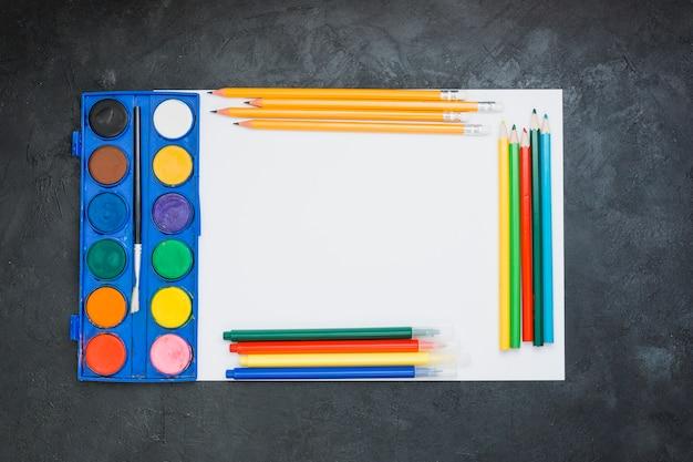 Malowanie sprzętu na arkuszu białego papieru na czarnym tle łupków