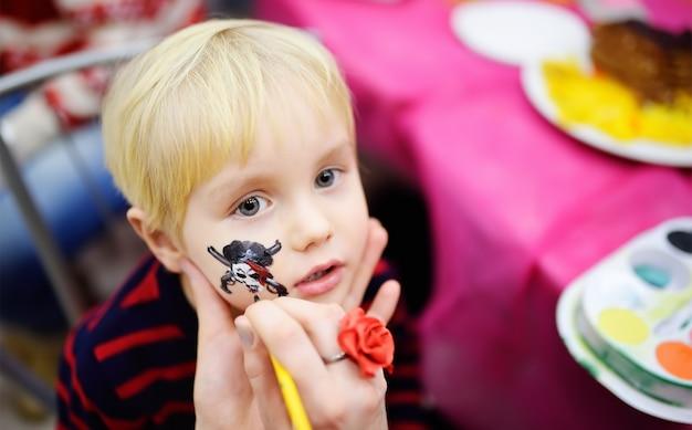 Malowanie twarzy dla małego chłopca podczas urodzinowego przyjęcia dla dzieci