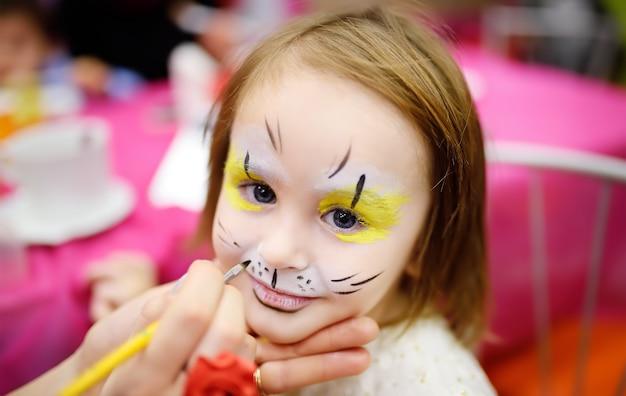 Malowanie twarzy dla uroczej małej dziewczynki podczas przyjęcia urodzinowego dla dzieci