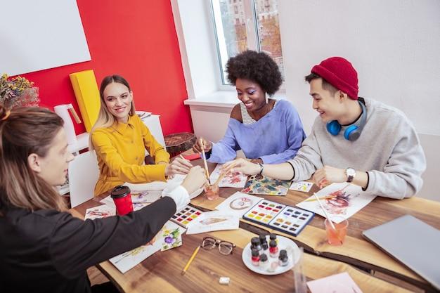 Malowanie uczniów. czterech studentów sztuki artystycznej maluje na białych kartkach papieru podczas zajęć z rysunku