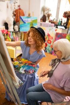 Malowanie w pobliżu nauczyciela. młody artysta kręcone rudowłosy na sobie długą sukienkę i kapelusz malowanie w pobliżu nauczyciela