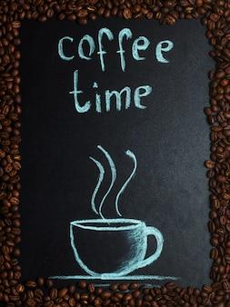Malowany kubek w ramce ziaren kawy.