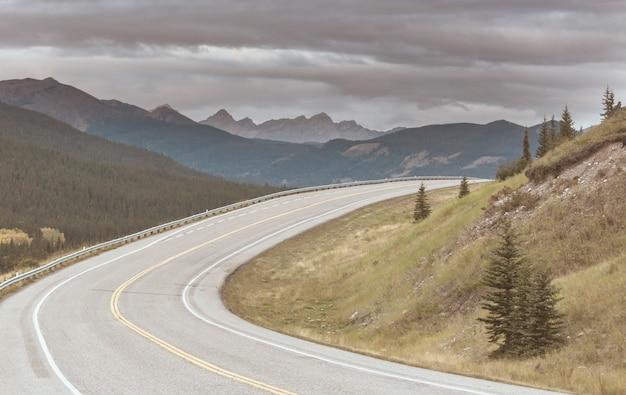Malownicza droga w górach. tło podróży. człowiek będzie na tle wschód słońca.