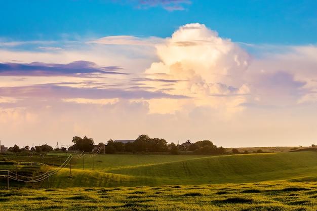 Malownicza, kręcona chmura nad łąką podczas wschodu lub zachodu słońca