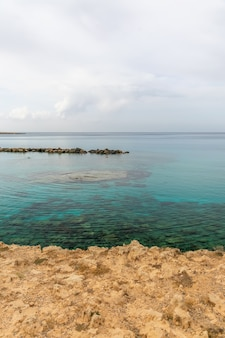 Malownicza plaża z krystalicznie czystą wodą znajduje się nad brzegiem morza śródziemnego.