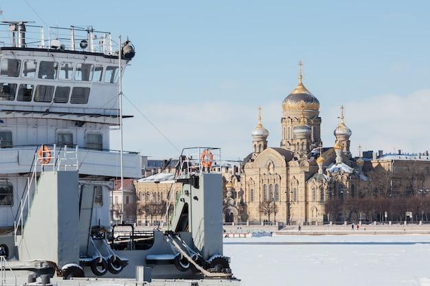Malownicza sceneria ze statkiem wojskowym przed kościołem wniebowzięcia najświętszej marii panny na nabrzeżu rzeki newy w sankt petersburgu w rosji