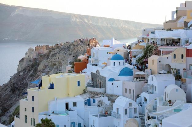 Malownicza wioska oia z turystami na pokaz zachodu słońca, wyspa santorini, grecja