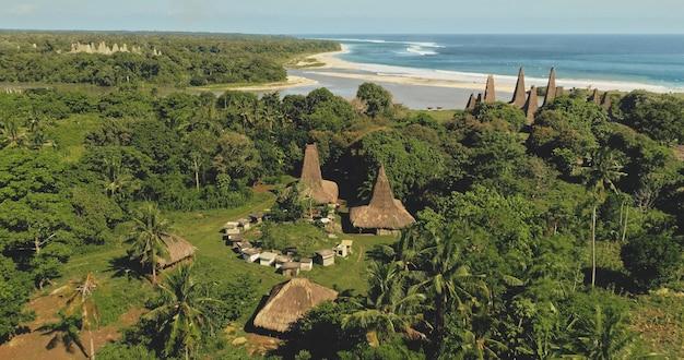Malownicza wioska z tradycyjnymi domami na piaszczystym wybrzeżu zatoki morskiej w widoku z lotu ptaka. zielony tropikalny krajobraz przyrody na ozdobnych dachach. niezwykłe budynki w prymitywnym osadnictwie indonezji