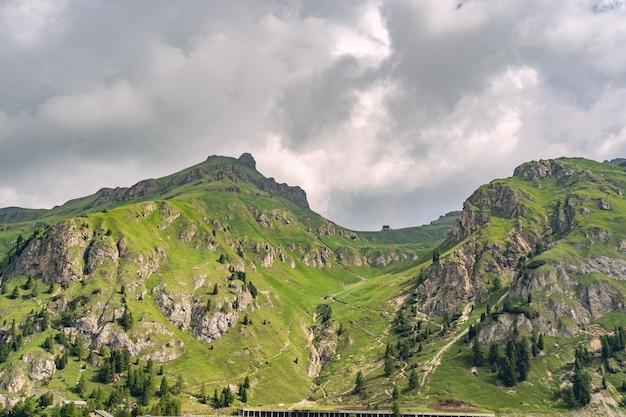 Malownicze alpy z zielonym wzgórzem pod zachmurzonym niebem