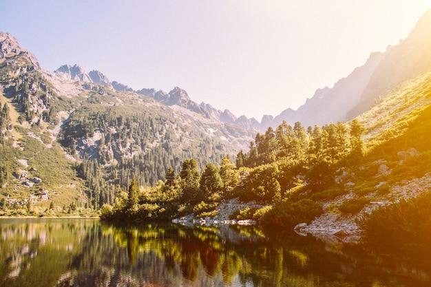 Malownicze górskie jezioro i zielony las. wysokie skały. piękny krajobraz.