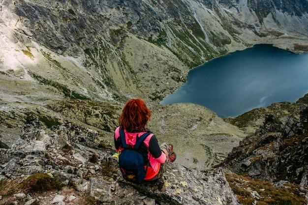 Malownicze górskie jezioro. wysokie skały. piękny krajobraz. podróżna kobieta siedzi na szczycie góry.