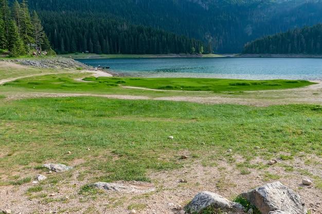 Malownicze jezioro z leśnym lasem i pięknymi górami z tyłu oraz błękitne niebo z chmurami