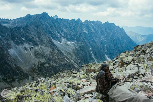 Malownicze krajobrazy gór. wysokie skały. piękny krajobraz. nogi podróżującego człowieka.