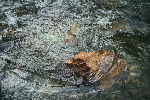 Malownicze tło natura z żywym pomarańczowym kamieniem w przezroczystej wodzie górskiej rzeki. kolorowe kamieniste dno pod czystą wodą. piękna przyroda tło z pomarańczowym głazem w górskiej potoku.