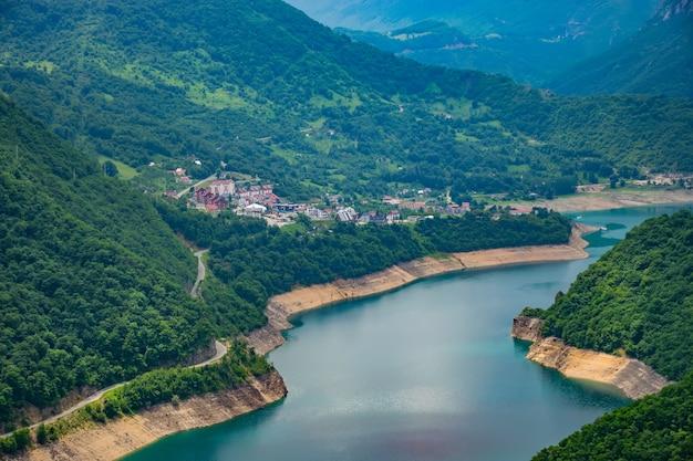 Malownicze turkusowe jezioro można zobaczyć ze szczytu wysokiej góry.