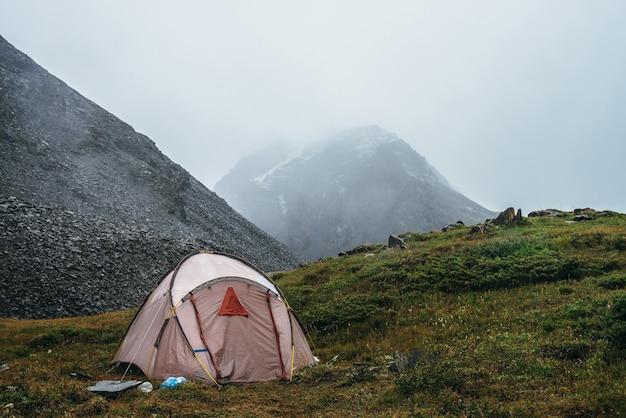 Malowniczy alpejski krajobraz z namiotem na zielonym wzgórzu wśród skał. piękne ośnieżone góry w niskich chmurach. klimatyczna sceneria z namiotem w górach przy pochmurnej pogodzie. wysokie góry pokryte śniegiem.
