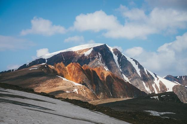 Malowniczy alpejski krajobraz z ośnieżonymi szczytami górskimi i jaskrawoczerwonymi ostrymi skałami pod błękitnym niebem z chmurami. kolorowa słoneczna górska sceneria ze śnieżnym szczytem i spiczastymi, pstrokatymi pomarańczowymi skałami.