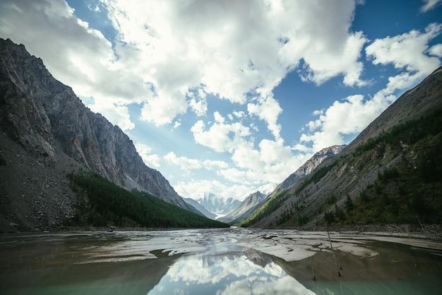 Malowniczy alpejski krajobraz z pięknym płytkim górskim jeziorem ze strumieniami w górskiej dolinie od zaśnieżonych gór pod zachmurzonym niebem. słoneczna górska sceneria z lustrzanym jeziorem polodowcowym w wysokich górach.