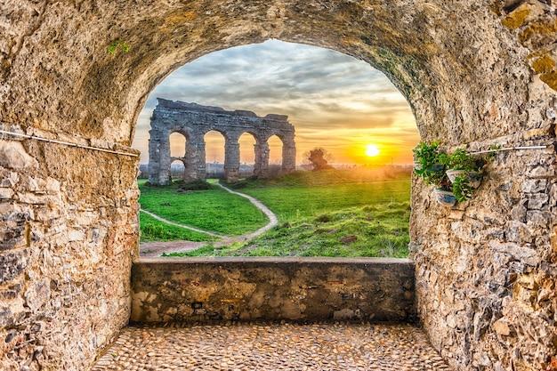 Malowniczy balkon w kształcie łuku skalnego z widokiem na słynne ruiny parco degli acquedotti w rzymie, włochy