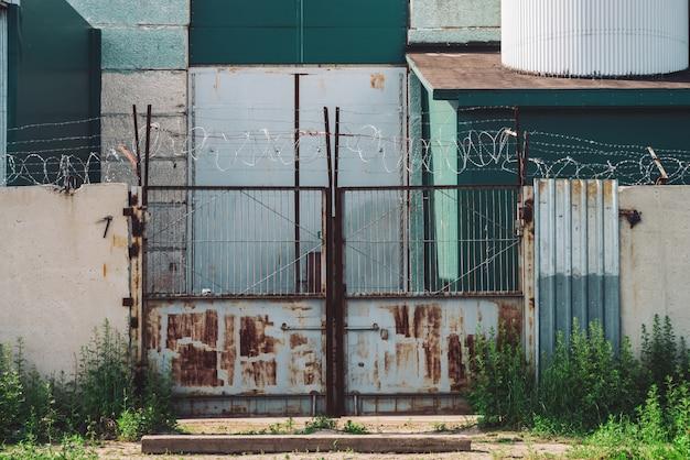 Malowniczy budynek przemysłowy z bliska. metalowa zardzewiała brama i betonowe ogrodzenie z drutu kolczastego. wejście do starej fabryki. obszar zamknięty stary obiekt przemysłowy porośnięty jest trawą. wysokie metalowe drzwi