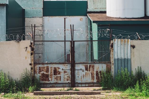 Malowniczy budynek przemysłowy z bliska. metalowa zardzewiała brama i betonowe ogrodzenie z drutu kolczastego. wejście do starej fabryki. obszar zamknięty