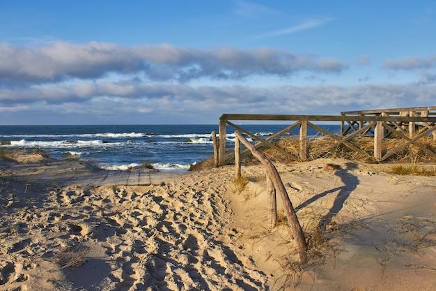 Malowniczy drewniany chodnik zejście do morza na wydmach. morze bałtyckie