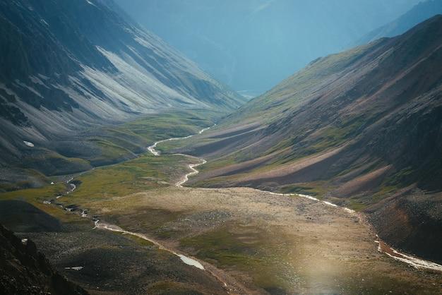Malowniczy górski krajobraz pstrokatej górskiej doliny z rzeką w złotym świetle słonecznym. wspaniała słoneczna góralska sceneria wielokolorowej doliny z górską rzeką i czerwonym zboczem. niezwykły krajobraz fantasy.