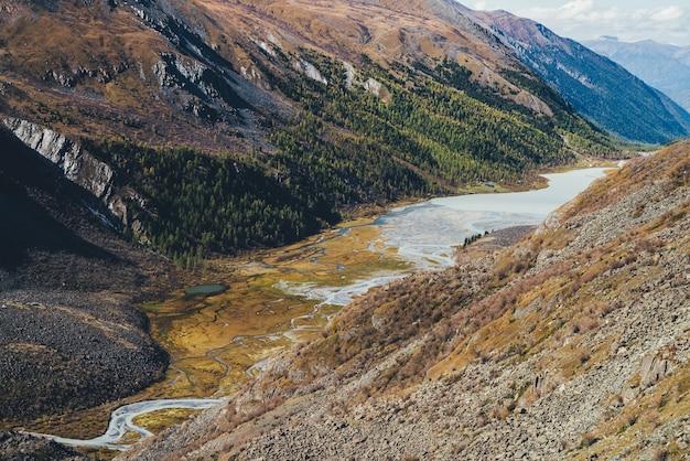 Malowniczy górski krajobraz z płytkim górskim jeziorem w wąskiej dolinie wśród wysokich gór w jesiennych kolorach w słońcu. niesamowity widok na alpejskie jezioro i las na zboczu góry w słońcu jesienią