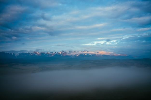 Malowniczy górski krajobraz z wielkim ośnieżonym pasmem górskim oświetlonym pomarańczowym słońcem świtu nad gęstą mgłą wśród niskich chmur o zmierzchu. niesamowita poranna sceneria z wysokim grzbietem górskim pod błękitnym pochmurnym niebem.