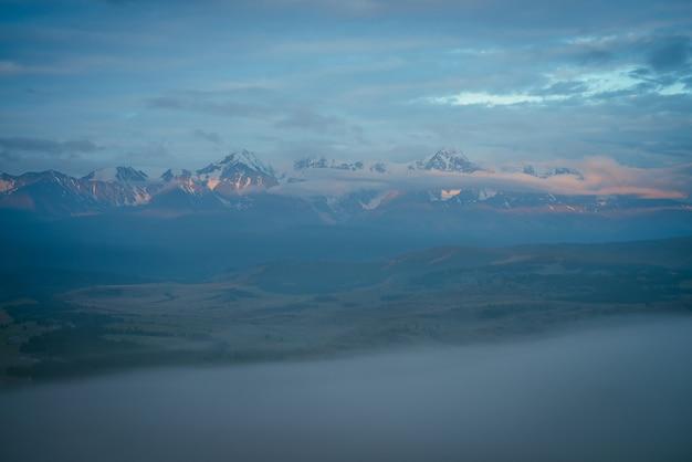 Malowniczy górski krajobraz z wielkim ośnieżonym pasmem górskim oświetlonym pomarańczowym słońcem świtu nad gęstą mgłą wśród niskich chmur o zmierzchu. niesamowita sceneria poranka z wysokim grzbietem górskim pod błękitnym pochmurnym niebem.