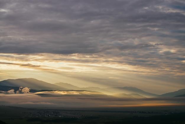 Malowniczy górski krajobraz ze złotymi niskimi chmurami nad wioską wśród sylwetek gór pod zachmurzonym niebem świt. nastrojowa alpejska sceneria wsi w niskich chmurach w rozświetlającym kolorze zachodu słońca.