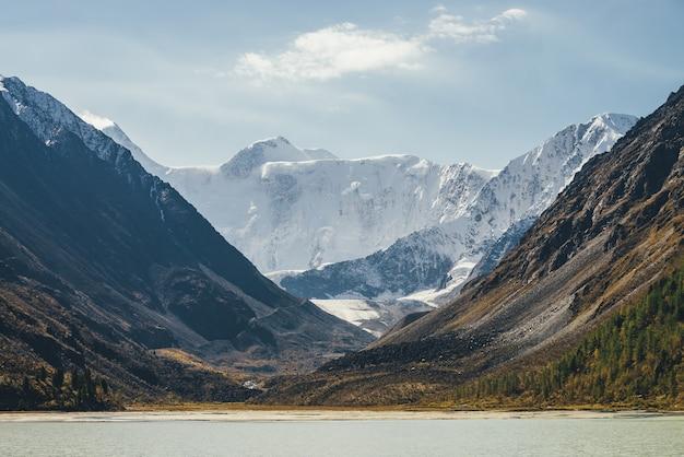 Malowniczy jesienny krajobraz z górskim jeziorem w dolinie i żółtymi modrzewiami na zboczu wzgórza z widokiem na wysoką ośnieżoną ścianę górską pod niebem z chmurami cirrus. niesamowita alpejska sceneria z wielką górą śnieżną.