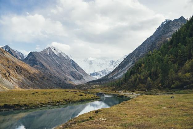 Malowniczy jesienny krajobraz z górskim potoku w dolinie z widokiem na dużą skałę ze śniegiem na szczycie i pięknymi wysokimi ośnieżonymi górami w słońcu. strumień z czystą wodą i wielkimi ośnieżonymi górami.