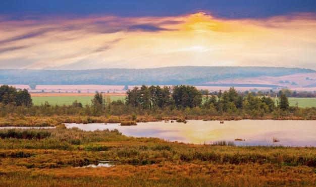Malowniczy jesienny krajobraz z rzeką i drzewami podczas zachodu słońca.