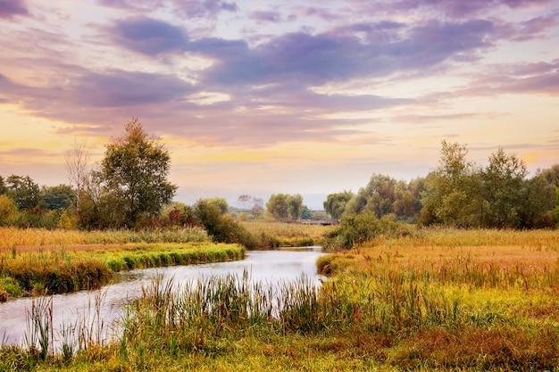 Malowniczy jesienny krajobraz z rzeką i zachmurzonym niebem o zachodzie słońca