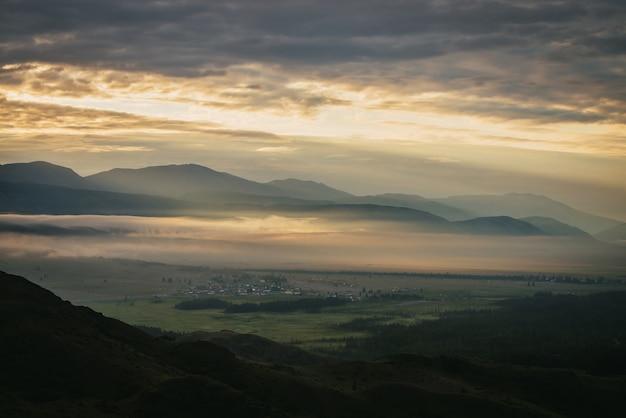 Malowniczy krajobraz górski ze złotymi niskimi chmurami nad wioską w górskiej dolinie wśród sylwetek gór pod zachmurzonym niebem świt. nastrojowe alpejskie krajobrazy wsi w pomarańczowych niskich chmurach.