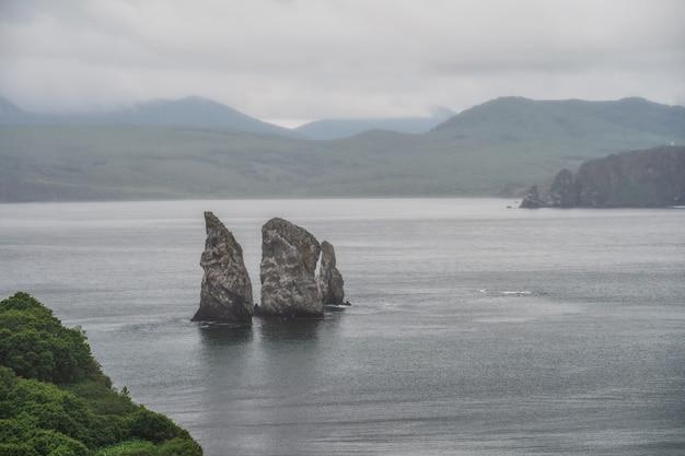 Malowniczy krajobraz kamczatki: scenerie skaliste wyspy na morzu z falami - three brothers rocks w avachinskaya bay (avacha bay) na oceanie spokojnym
